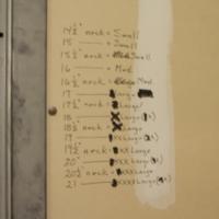 Attendant uniform sizing chart on wall in basement